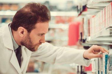Handsome pharmacist at work