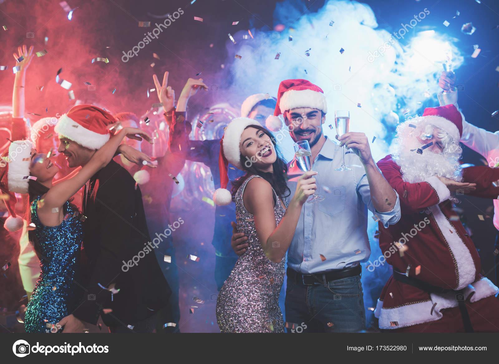Joven pareja bailando con copas de champán en las manos. Detrás de ...
