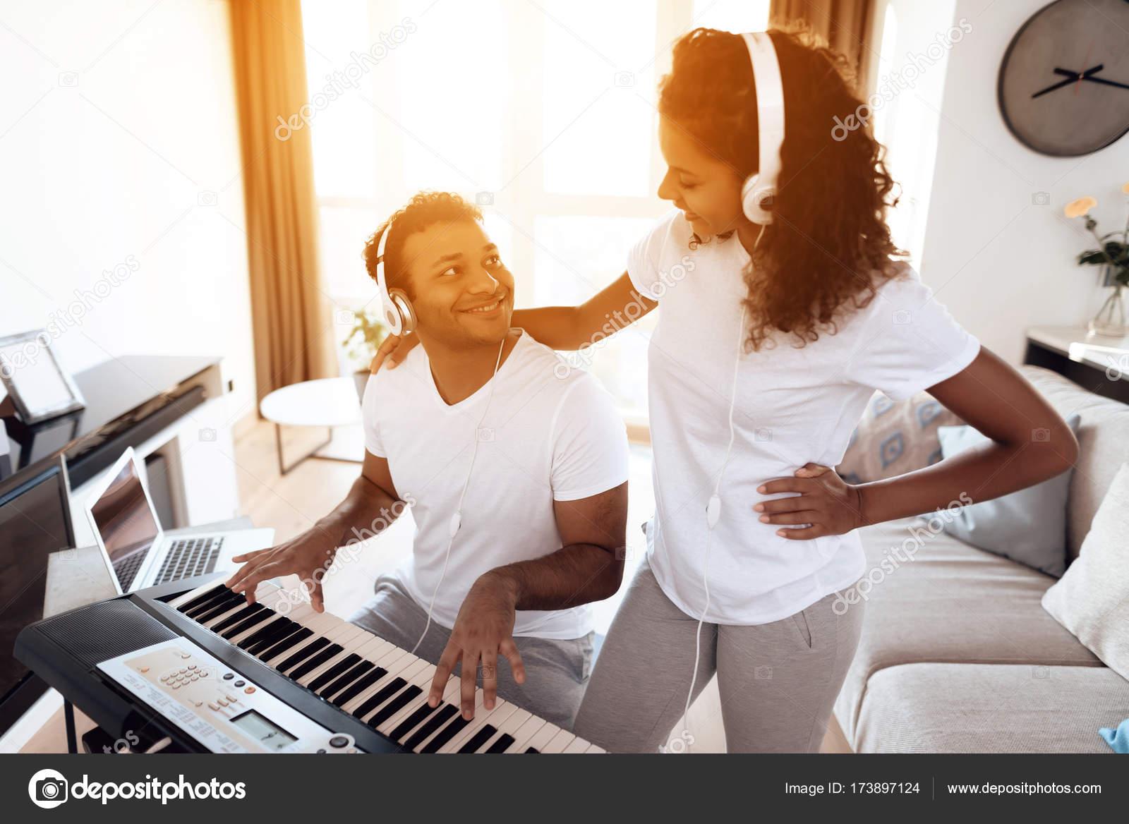 Ein schwarzer Mann sitzt im Wohnzimmer seiner Wohnung und spielt ...