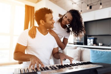 A black man sits in the living room of his apartment and plays a synthesizer. Nearby is his girlfriend and hugs him.