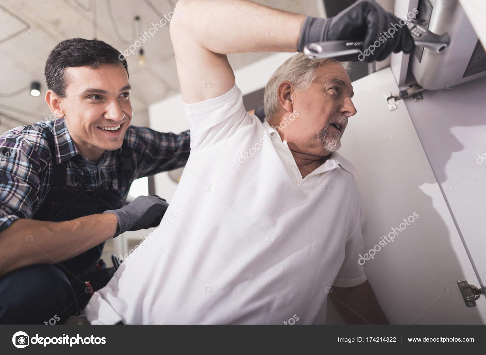 Zwei Klempner vorbereitet, die Küchenspüle zu reparieren. Einer von ...