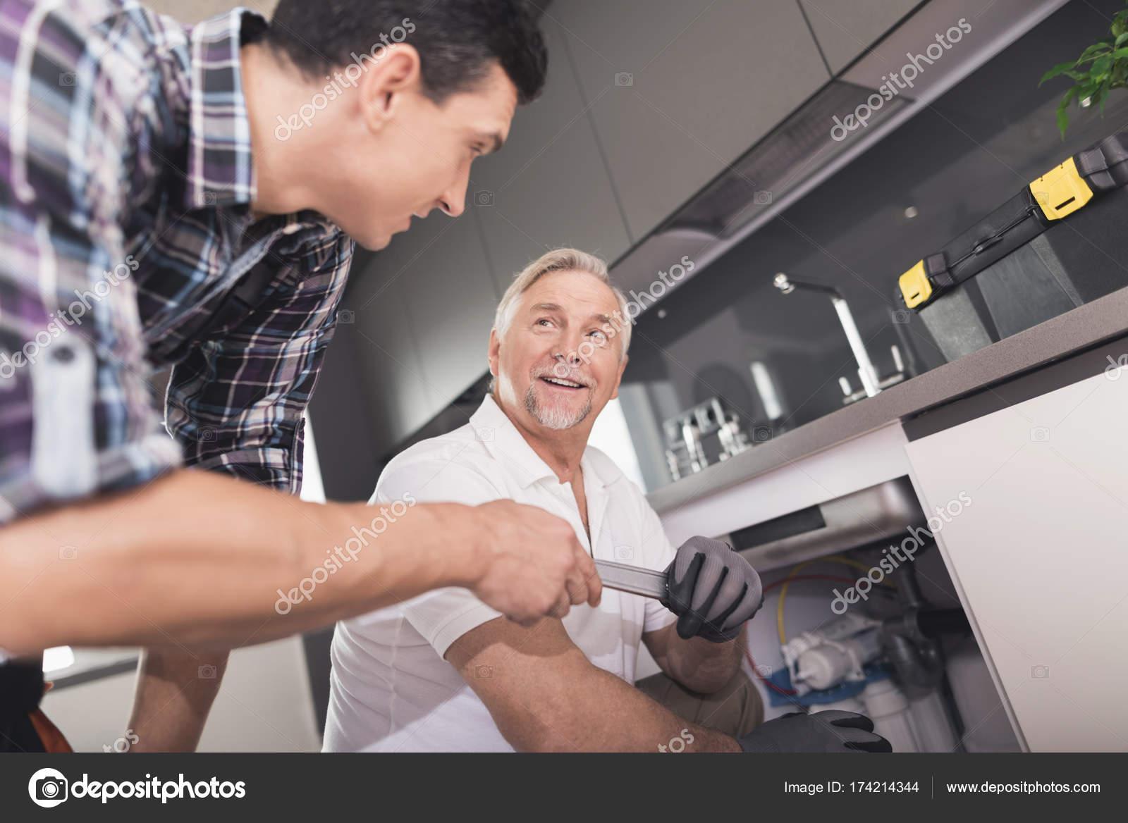 Zwei Klempner vorbereitet, die Küchenspüle zu reparieren. Dazu zählt ...