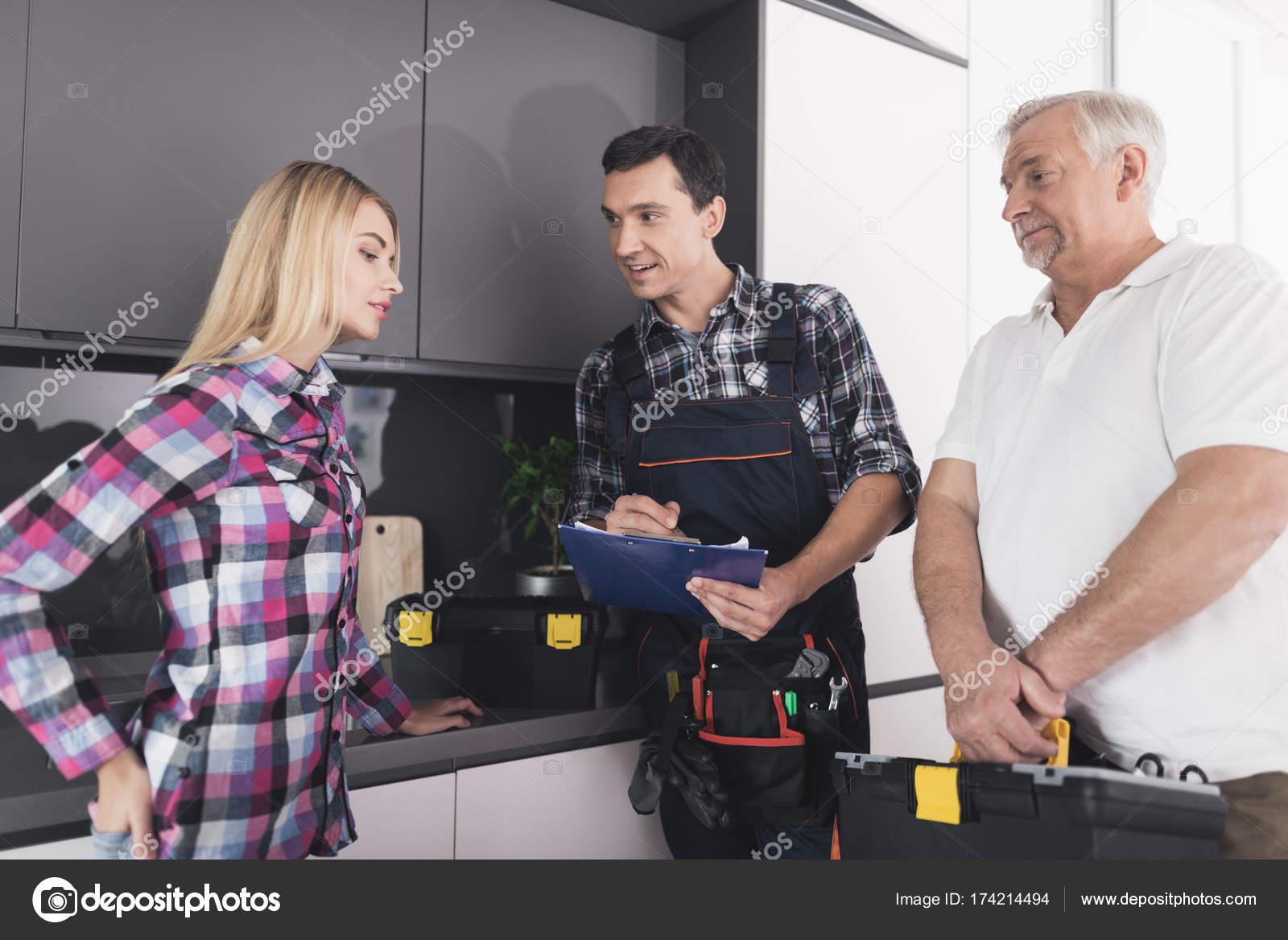 Die Frau rief zwei Klempner, die Küchenspüle zu reparieren. Die ...
