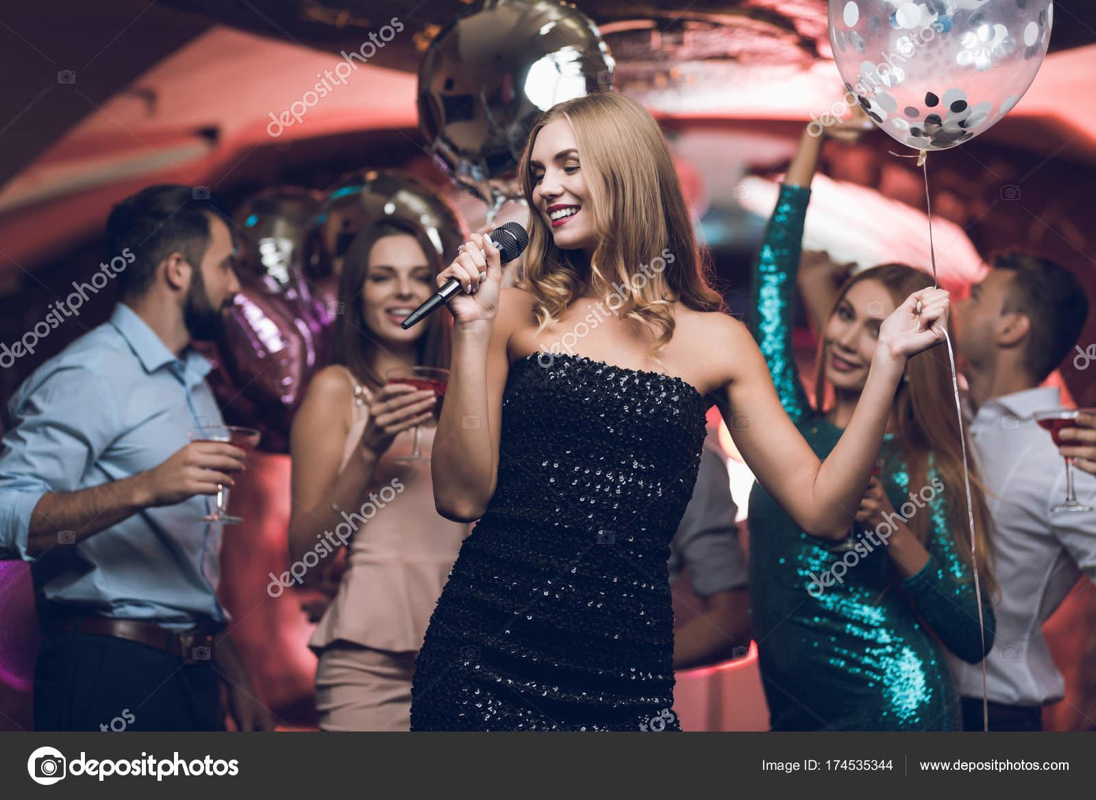 Jugendliche haben Spaß in einem Nachtclub und Karaoke singen. Im ...