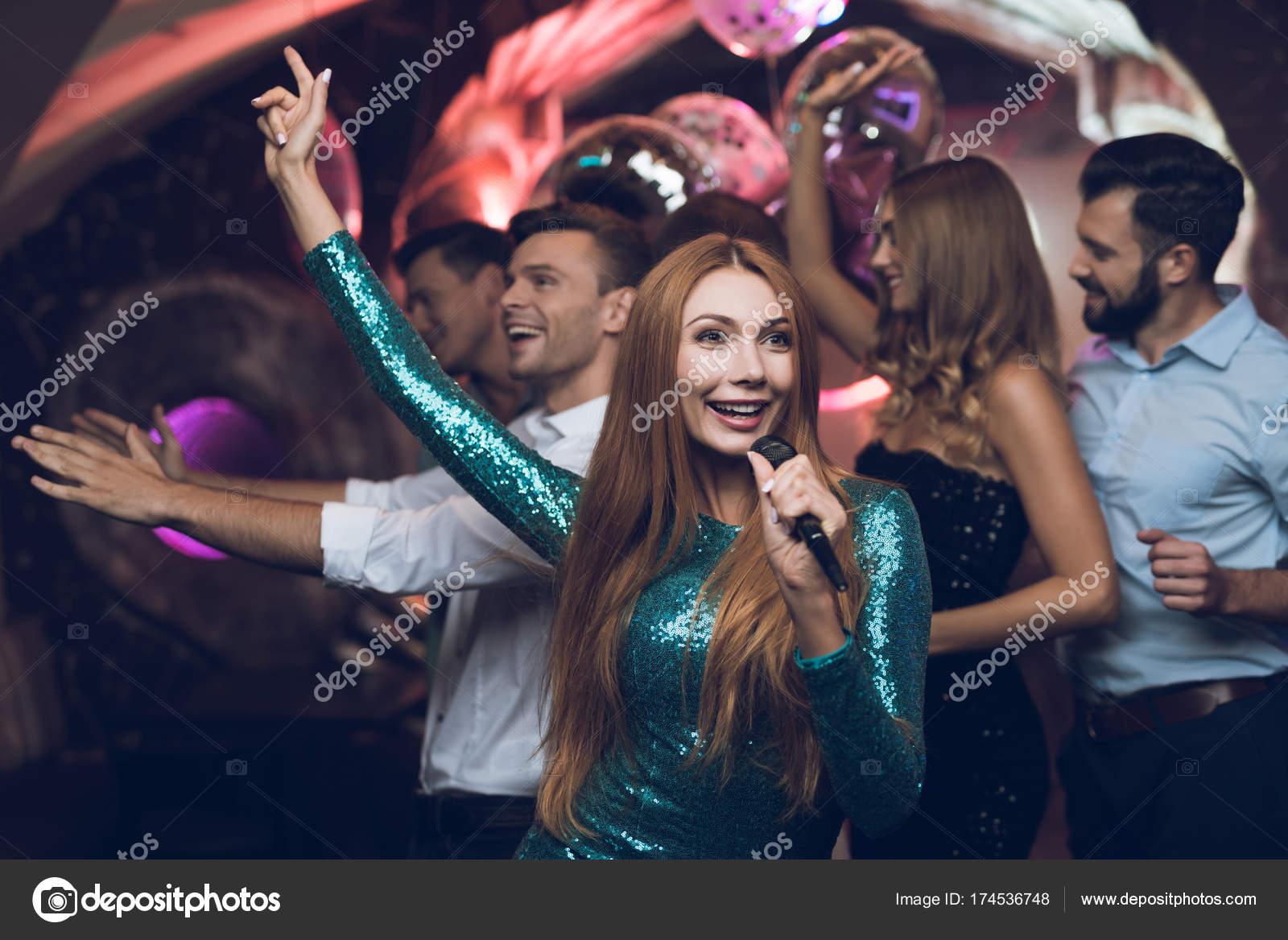 Una mujer en un vestido verde es cantar canciones con sus amigos en ...