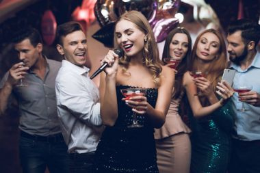 A woman in a black dress is singing songs with her friends at a karaoke club. Her friends have fun on the background.