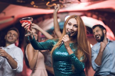 Young people have fun in a nightclub and sing in karaoke. In the foreground, a woman in a green dress.