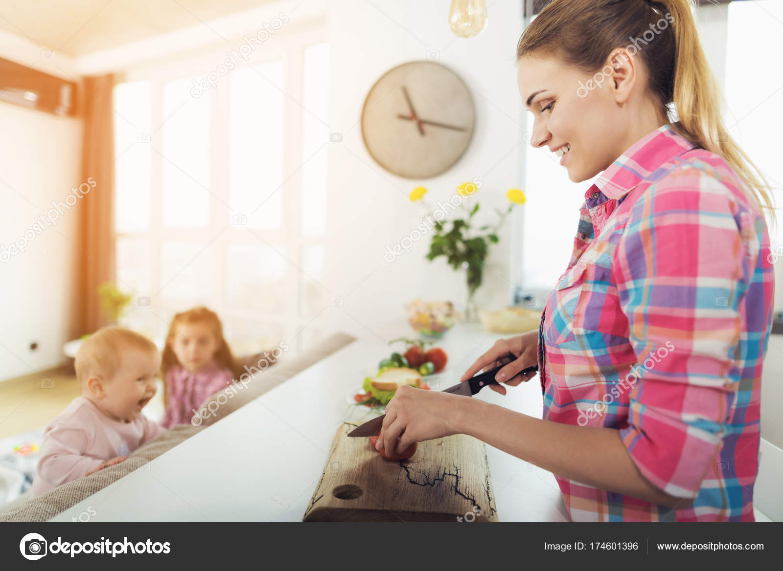 Mom cooks in the kitchen while her children play next to her on the ...
