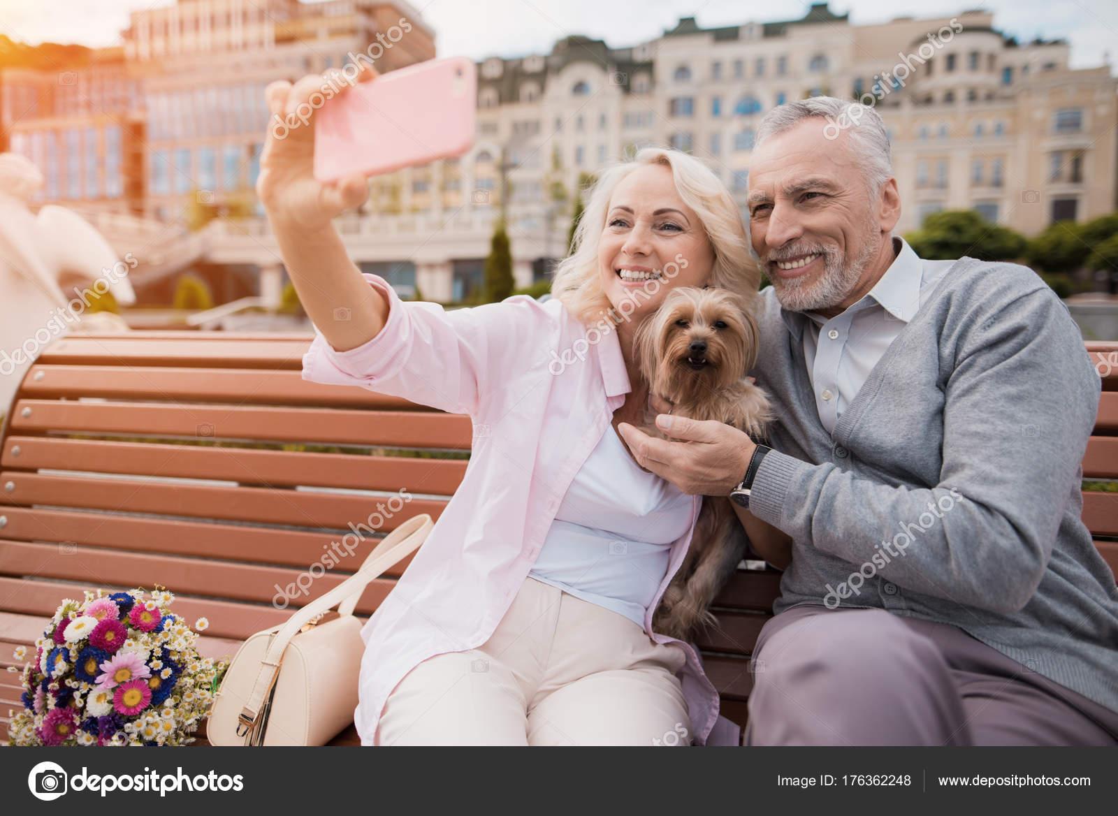 Ein älteres Ehepaar spaziert auf dem Platz mit ihren kleinen Hund ...