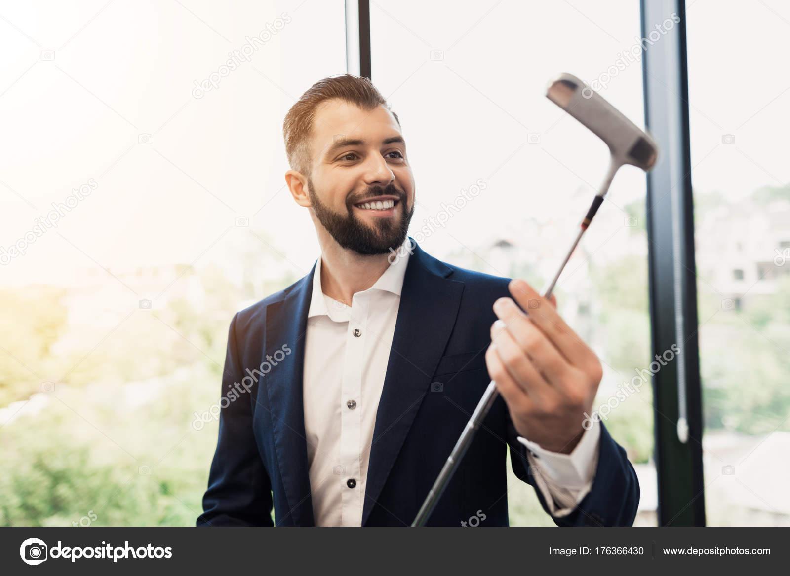 Un homme dans un costume noir respectable examine un club de golf