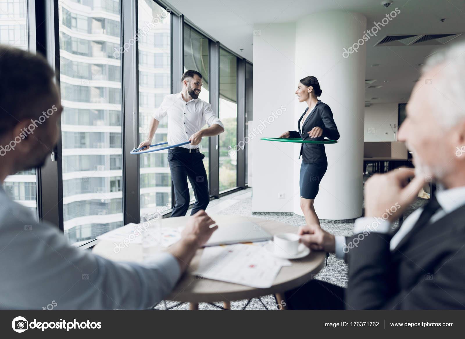 Kul på kontoret. En man och en kvinna twist hula hoops. Två av sina  kollegor sitta vid bordet och titta på dem. På bakgrund av ett stort  panoramafönster med ... 76337c9b9de3c