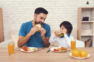 A man spends time with his son. The father of boy is engaged in raising child. Father feeds his son. The boy is having breakfast with his father.