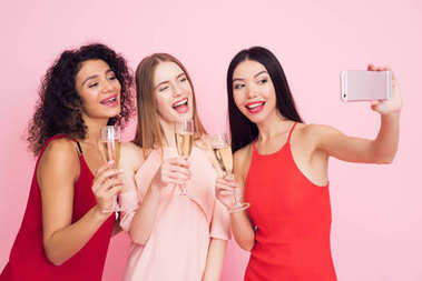 Three girls in white and red dresses with champagne taking selfie on pink background celebrating women's day March 8.