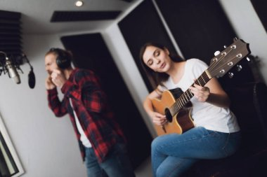 A man and a woman sing a song at a recording studio. A man sings, and a woman plays the guitar.