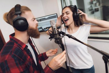 A man and a woman sing a song in a modern recording studio. On the man is a red checked shirt, on a woman a white T-shirt. stock vector