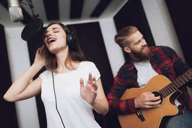 A girl and a guy sing a song to a guitar in a modern recording studio. The girl sings, and the guy plays the guitar.