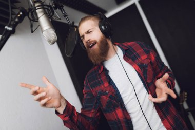 A man with a beard performs a song in a recording studio. He wears a plaid shirt. In front of him is a studio microphone. He sings enthusiastically.