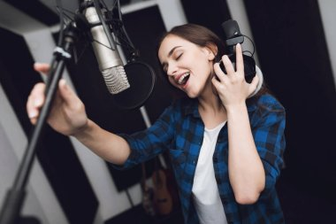The girl sings her song in a modern recording studio. She sings the song very emotionally. In front of her is a studio microphone.