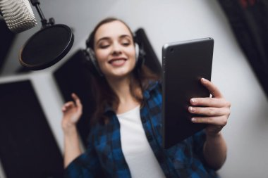 The girl in the recording studio sings a song. She has headphones on her head, and a tablet with text in her hands. Next to her is a microphone. She emotionally sings the song.