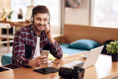 Freelancer man listening to music at laptop sitting at desk.
