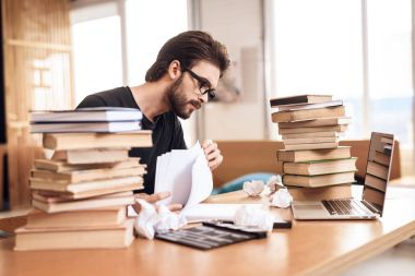 Freelancer bearded man taking notes sitting at desk surrounded by books.