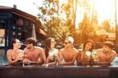 Fotografie Unternehmen der happy Friends trinkt Cocktails im Pool im Sommer. Swimming Pool-Party. Multiethnische Gesellschaft von Freunden im Schwimmbad