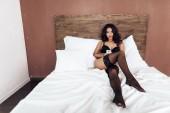 Krásná vášnivá žena v spodní prádlo a punčochy leží na posteli s telefonem v ložnici. Touha a pokušení