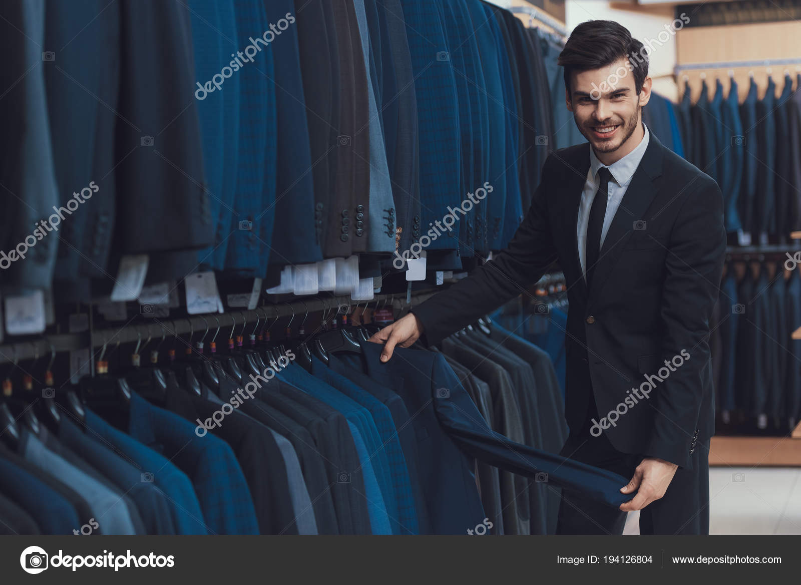 9003f834 Confident young man looks at jackets for sale in showroom of men business clothing  store. Boutique of business suits — Photo by vadimphoto1@gmail.com