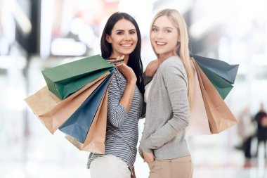 Young girlfriends with shopping bags are shopping at mall.
