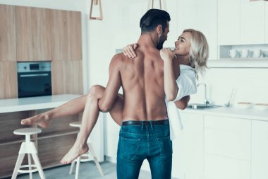 Handsome, brawny man is holding woman on arms at kitchen.