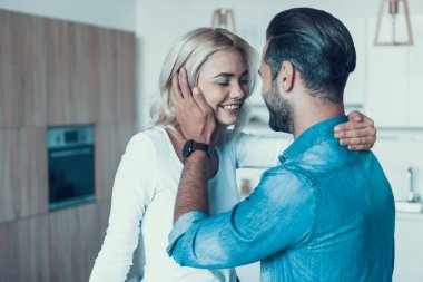 Loving happy couple together in kitchen.