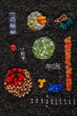 multi-colored beads, the pattern is laid out on black sand,white, green, yellow, blue, red