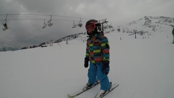 Malý chlapec v Alps.Son lyžování, po lyžování. Se učí lyžovat se svými rodiči.