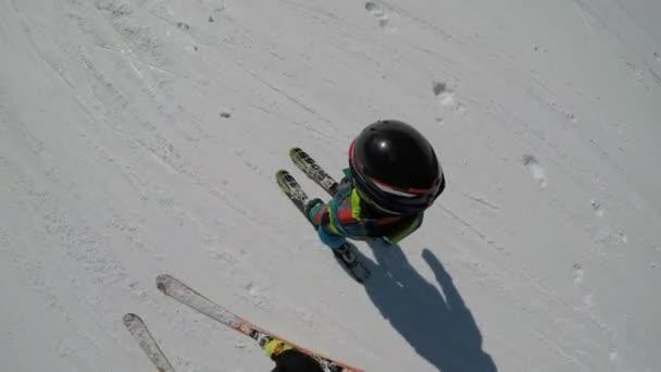 Kleiner Junge beim Skifahren in den Alpen. Sie lernen das Skifahren mit ihren Eltern.