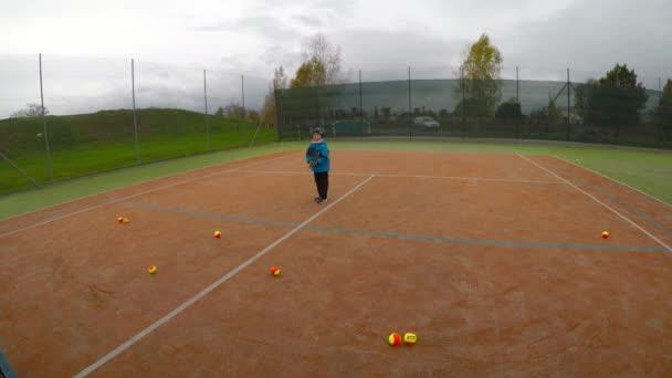 Malý chlapec hrát tenis. Tenisový trénink pro dítě. Tenis lekce forhend beckend