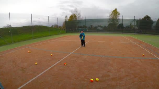 Malý chlapec hrát tenis. Tenisový trénink pro dítě. Tenis lekce forhend beckend.