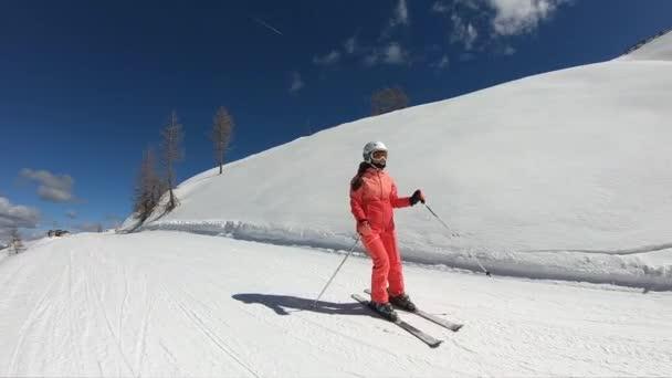 Pěkná ženská lyžování. Mladá dívka si užívá lyžování. Mladá dívka tráví aktivní dovolenou v rakouských Alpách. Stabilizované záběry. Zpomalený pohyb.