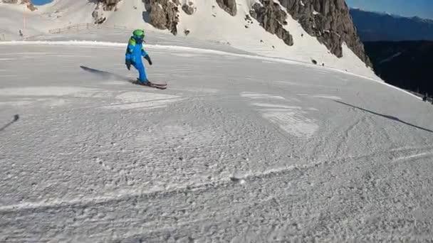 Malej kluk lyžuje. Šestileté dítě si užívá zimní dovolenou v alpském letovisku. Stabilizované záběry. Zpomalený pohyb.