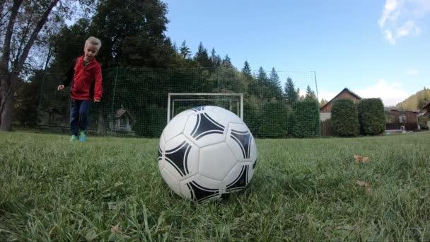 Kleine Kinder spielen Fußball. Der Junge schießt auf den Torwart und jubelt über das Tor. Der Junge rennt mit dem Ball zum Tor.