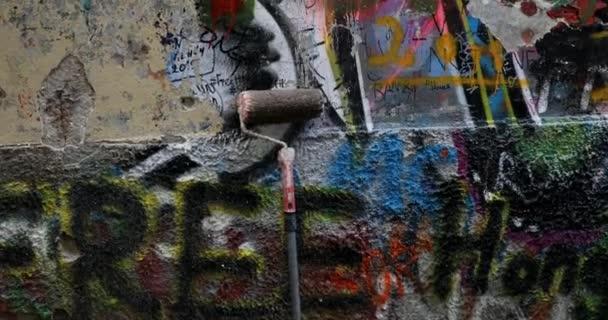 Odstranění graffiti z malované zdi. Dělník čistí natřenou stěnu od postřikovačů.