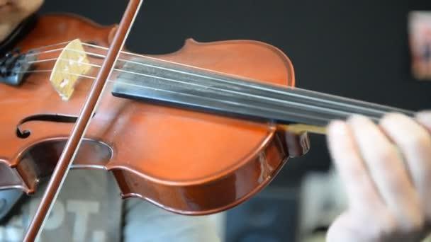 A zenész hegedül.