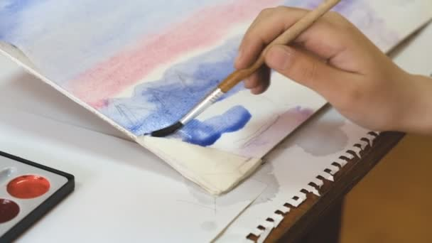 The child learns to paint with watercolors.