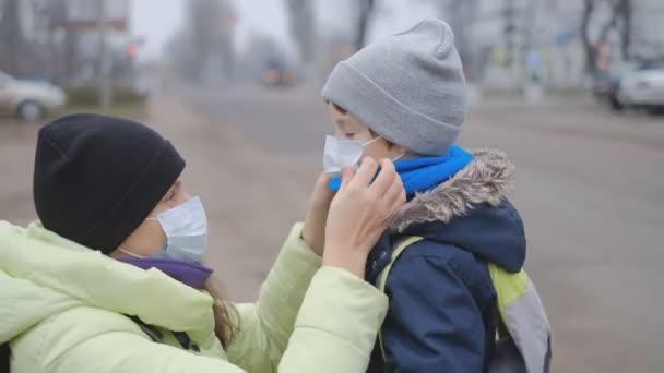 Schutz vor dem chinesischen Coronavirus in einer europäischen Stadt. Mutter korrigiert einem kleinen Sohn auf der Straße eine medizinische Schutzmaske.