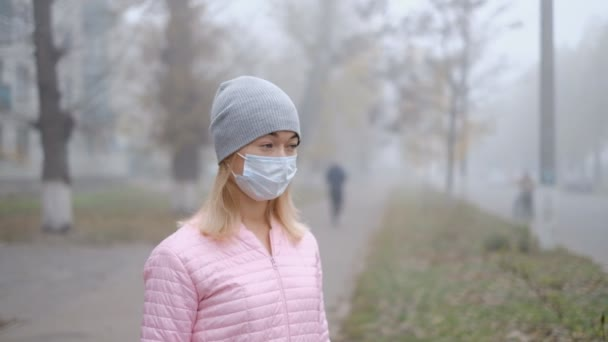 Protection against Chinese coronavirus in a European city. A young woman in a public place stands in a medical mask in Germany. The onset of symptoms of coronavirus.