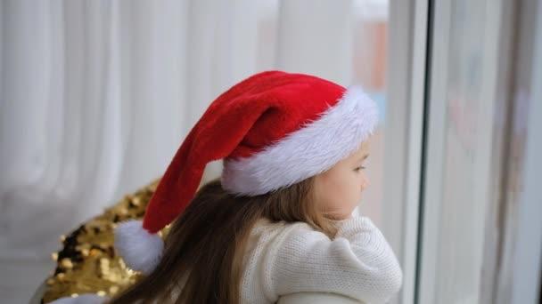 Ein kleines Mädchen mit Weihnachtsmütze sitzt am Fenster und wartet auf Weihnachten und Neujahr.