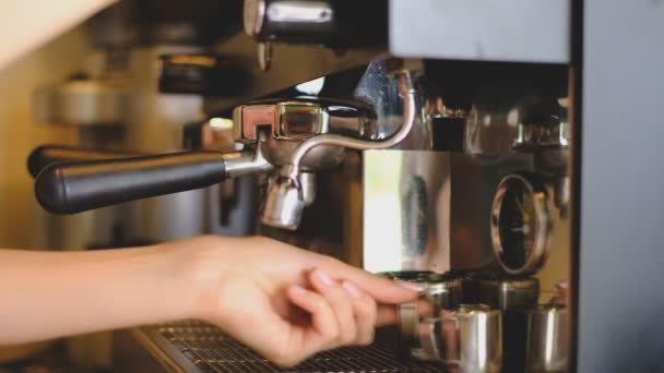 Making coffee using a coffee machine in a cafe.