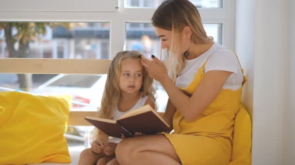 A young mother and little daughter are reading a book together.