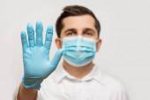 Orvosi egyenruhás, kék védőmaszkos és stoptáblát viselő kesztyűs orvos portréja.