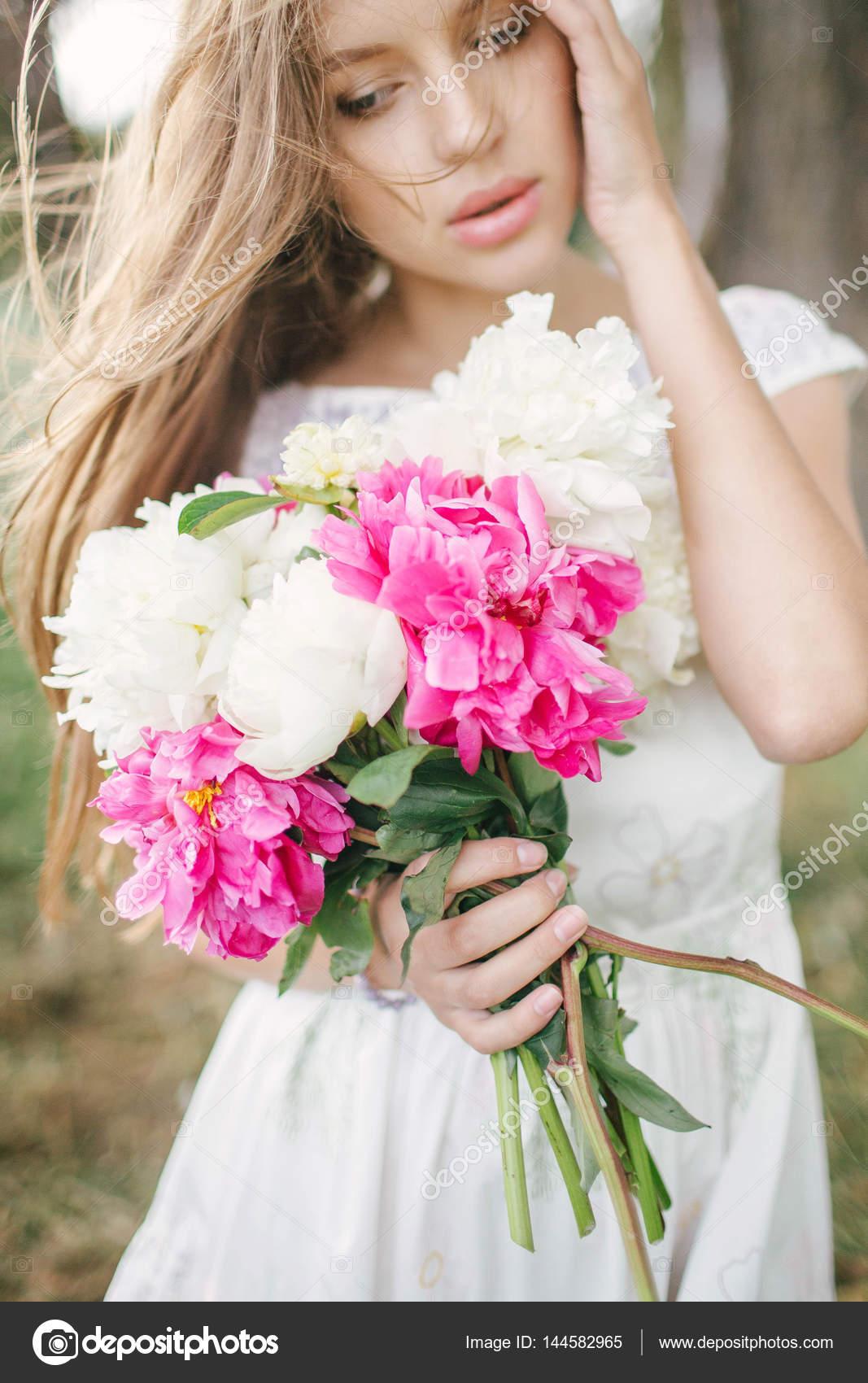 Hermosa mujer joven en vestido blanco al aire libre con flores ...