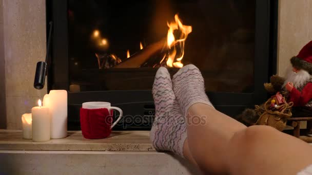Žena sedí s šálkem horkého nápoje a knihu u krbu